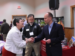 Kim LaMendola, of STW, shaking hands with Judson Reid, Cornell's Vegetable Specialist