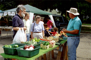 Chuck Couture talking with farmers market customers